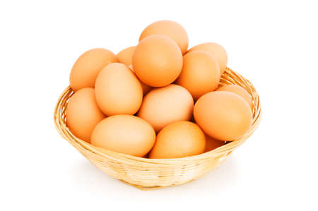Brown eggs in the basket on white photo