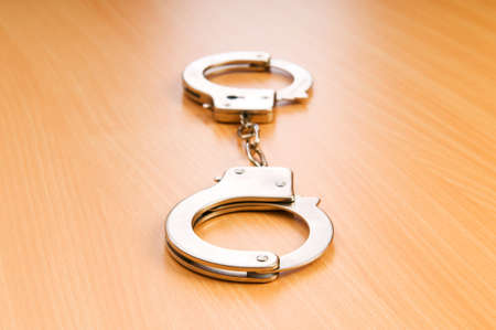 Metal handcuffs on the wooden background Stock Photo - 7634850