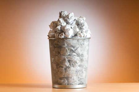Mülltonne mit Papier verschwenden isoliert auf weiss