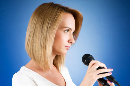 Girl singing with microphone against gradient background Stock Photo - 7641123
