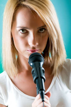 Girl singing with microphone against gradient background Stock Photo - 7641148
