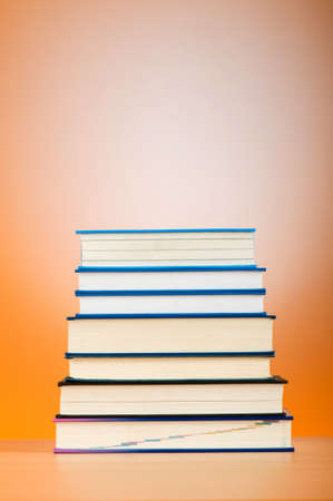Stack of text books against gradient background photo