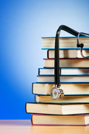 Books and stethoscope against the gradient background