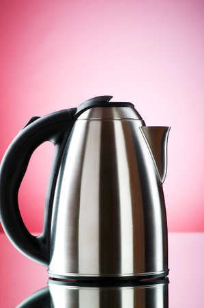 Shiny kettle against the colorful gradient background photo