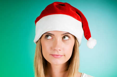 Girl with santa hat against gradient background photo