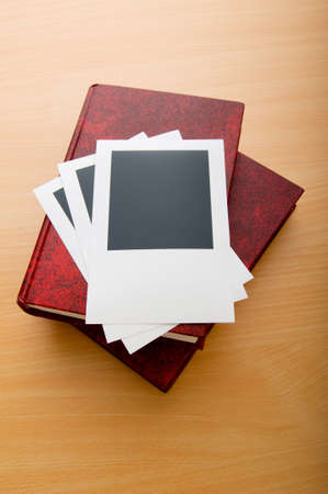 Books and blank photos on wooden table Stock Photo - 7867886