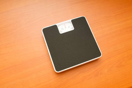 Dieting concept with scales on the wooden floor Stock Photo - 7867682