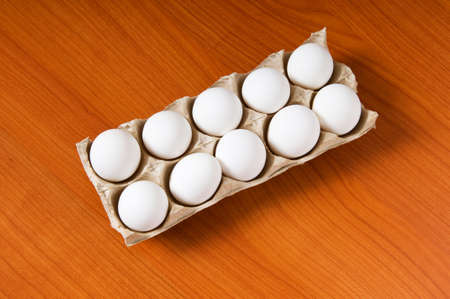 Many white eggs on the wooden table photo