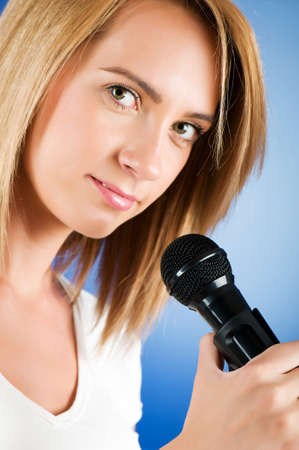 Girl singing with microphone against gradient background photo