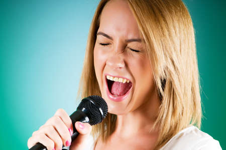 Girl singing with microphone against gradient background Stock Photo - 7941343