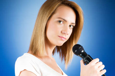 Girl singing with microphone against gradient background Stock Photo - 7941366