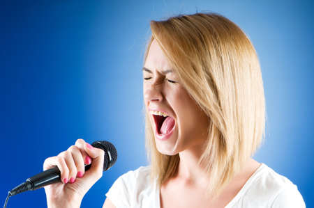 Girl singing with microphone against gradient background Stock Photo - 7941365