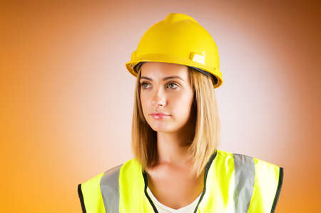 Young girl with hard hat against background photo