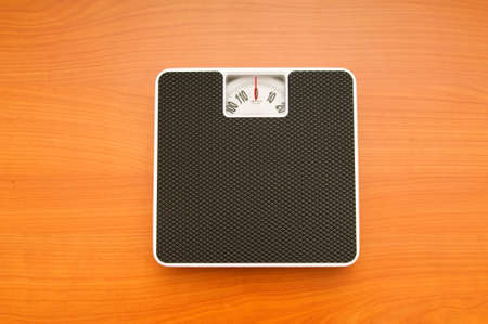 Dieting concept with scales on the wooden floor Stock Photo - 8028197