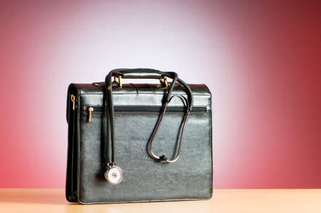 tool bag: Doctors case with stethoscope against colorful background Stock Photo