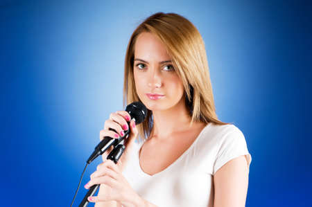 Girl singing with microphone against gradient background Stock Photo - 8054812