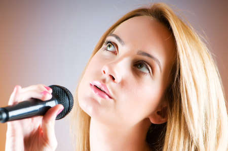 Girl singing with microphone against gradient background Stock Photo - 8037630