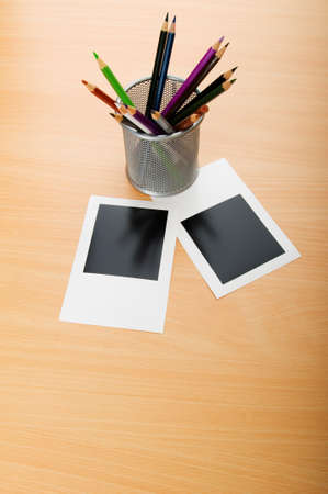 Blank instant photos and pencils on the wooden table photo