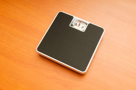 Dieting concept with scales on the wooden floor Stock Photo - 8137577