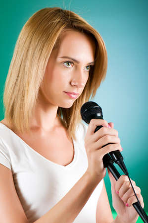 Girl singing with microphone against gradient background Stock Photo - 8163106