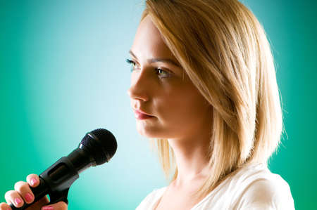 Girl singing with microphone against gradient background Stock Photo - 8163102