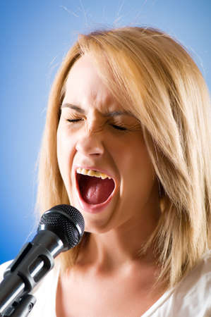 Girl singing with microphone against gradient background Stock Photo - 8163105