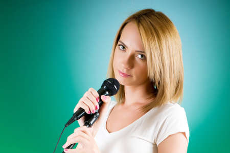 Girl singing with microphone against gradient background Stock Photo - 8375435