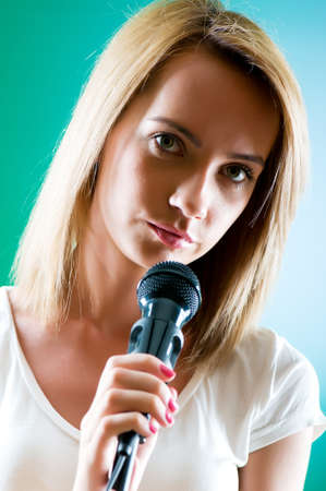 Girl singing with microphone against gradient background Stock Photo - 8375437