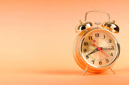 Time concept - alarm clock against colorful background photo