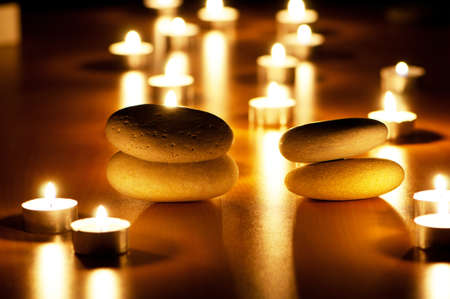 scented candle: Burning candles and pebbles for aromatherapy session