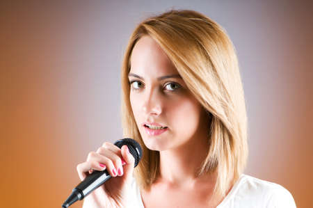 Girl singing with microphone against gradient background Stock Photo - 8375415