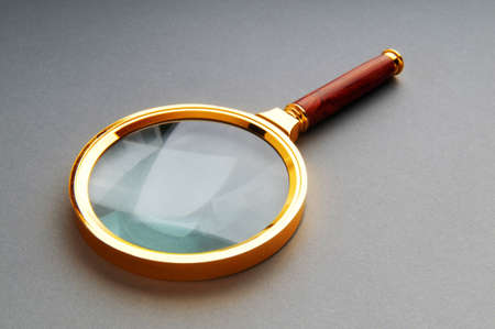 Magnifying glass with wooden handle on the flat surface photo