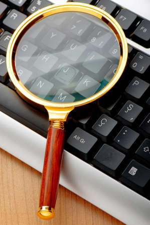 search solution: Computer security concept with keyboard and magnifying glass Stock Photo