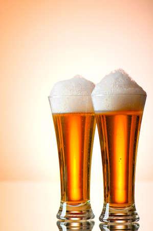 ámbar: Vasos de cerveza contra el fondo degradado multicolor