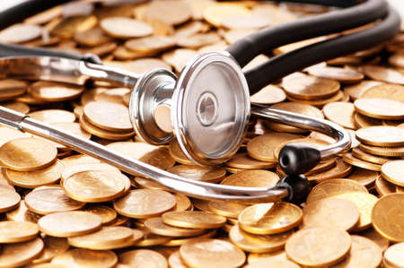monies: Concept of expensive healthcare with coins and stethoscope