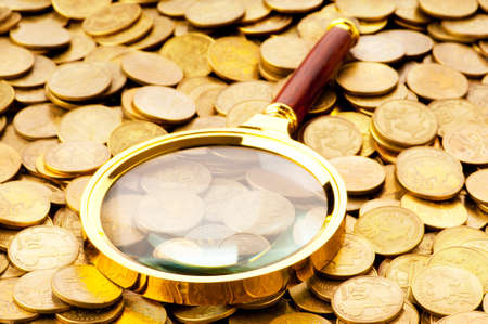 Magnifying glass and coins at the background photo