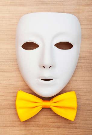 Masken und Fliege auf dem hölzernen Hintergrund