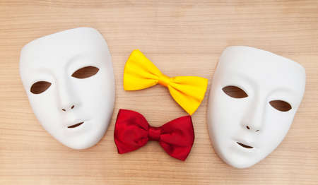 Masks and bow ties on the wooden background photo