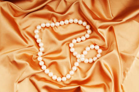 Pearl necklace on the bright satin background photo