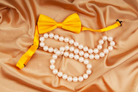 Bow ties and pearl necklace on the satin photo