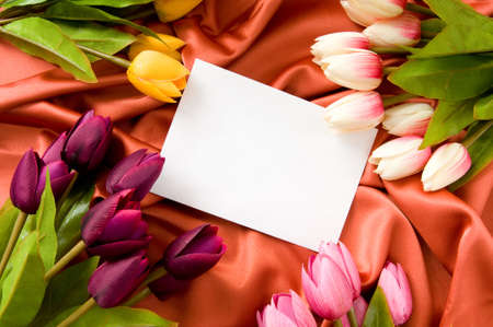 red tulips: Envelope and flowers on the satin background