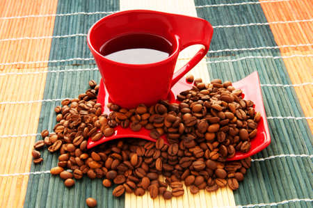 Cup of coffee with many beans around photo
