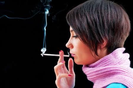 Young girl smoking on black photo