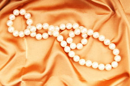 Pearl necklace on the bright satin background Stock Photo