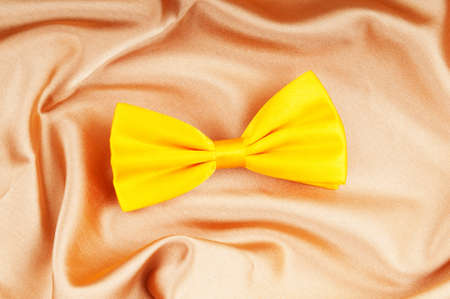 Bow ties on the bright satin background photo