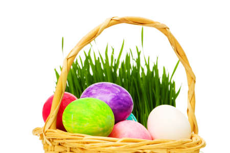 Eggs in the basket and grass isolated on white photo