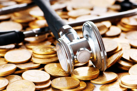 Concept of expensive healthcare with coins and stethoscope photo