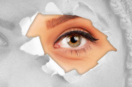 Woman eye through hole in paper photo