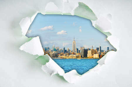 tearing down: New York city through hole in paper