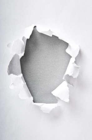 gescheurd papier: Gat in de papier met gescheurde zijden Stockfoto